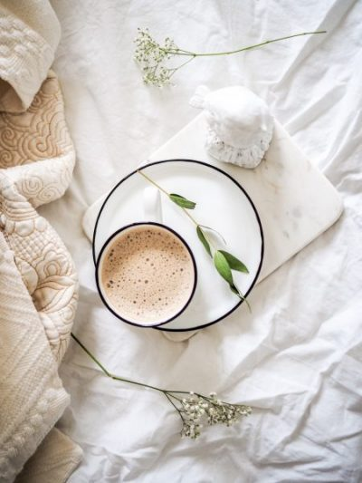 Flat lay of a fresh cup of coffee being served in bed