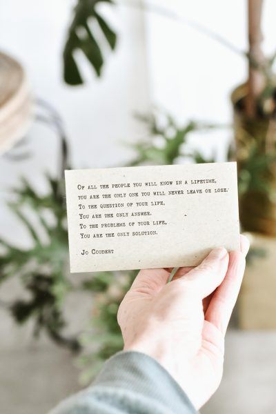 A hand holding a cue card with a few lines written by Jo Coudert
