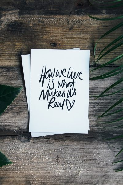 """A piece of paper that says """"how we live is what makes us real"""" on a wooden surface with leaves on both sides"""