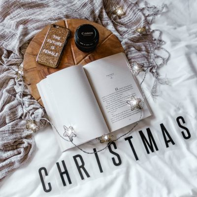 "Flatlay of someone's bed with an open book, some lights, a canon lens, a cellphone case that says ""The Futer is Female"" and words that say ""Christmas"""