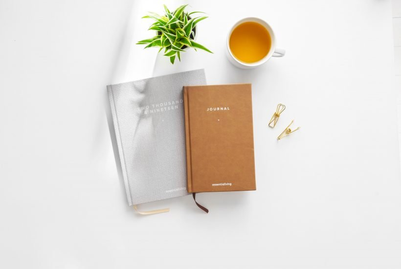 Flatlay of a plant, tea in a cup, a grey agenda with 2019 written on it and a beige journal on top of it